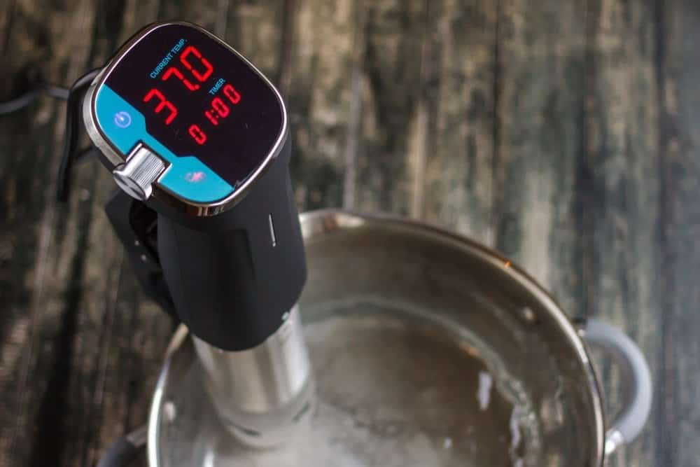 immersion circulator display showing temperature and timer attached to steel pot