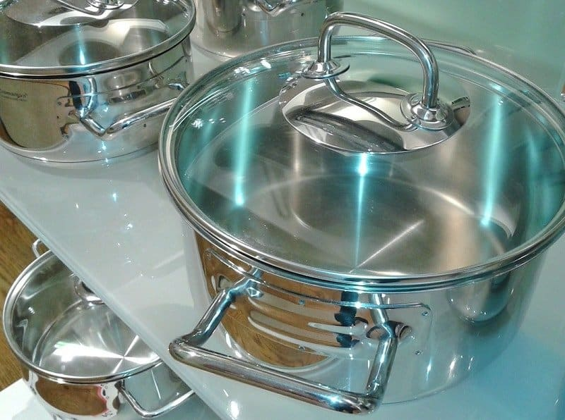 steel pots with glass lids on shelf