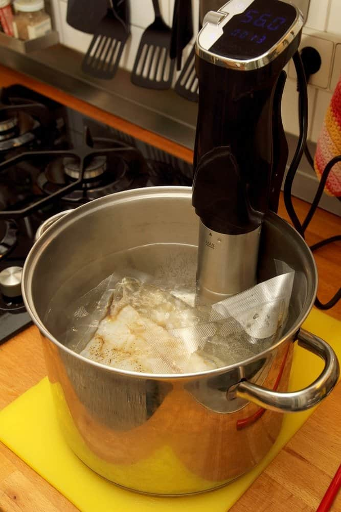 meat in sous vide bag in steel pot with immersion circulator on kitchen counter