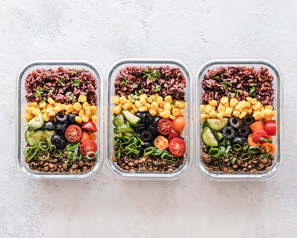 three meal prep containers in a row filled with food