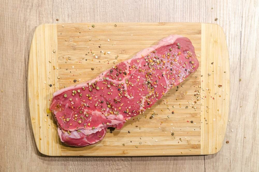raw steak on chopping board with seasoning sprinkled on top