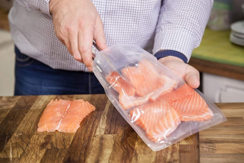 person putting pieces of salmon in sous vide bag