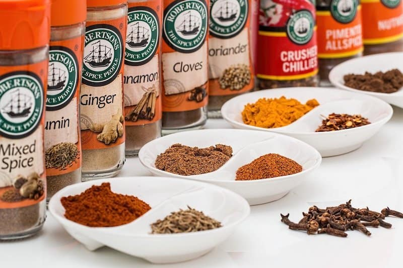 spices bottles in a line with plates in front of them with spices piled in them