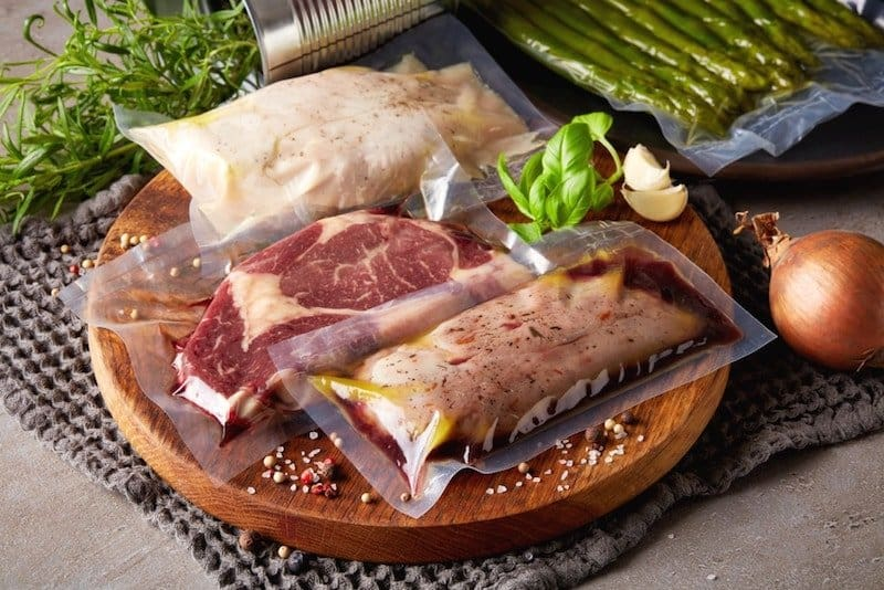 fish chicken and steak in sous vide bags on cutting board