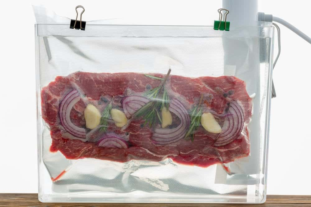 steak in sous vide bag clipped to side of container with sous vide cooker