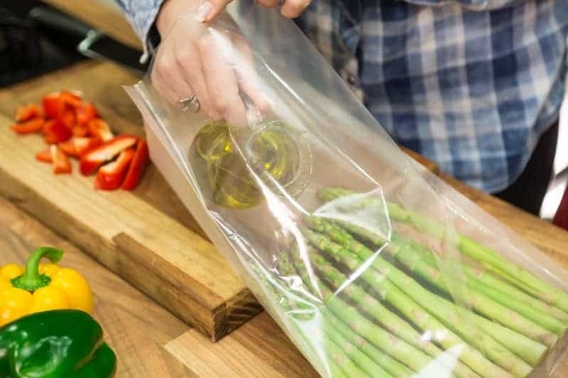 person pouring olive oil into sous vide bag with asparagus