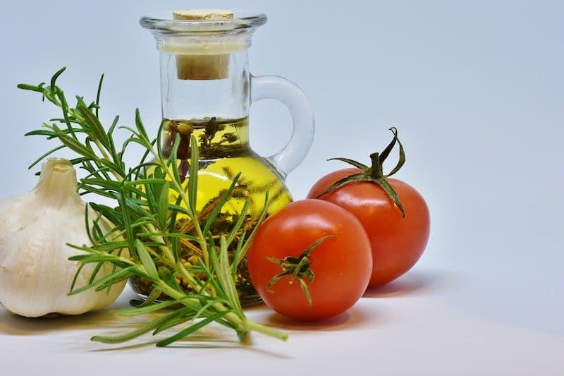 bulb of garlic, tomatoes, rosemary next to small jug of olive oil