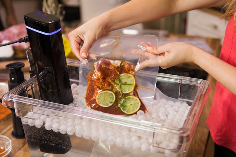 women lowering sous vide bag with piece of meat into container with ping pong balls