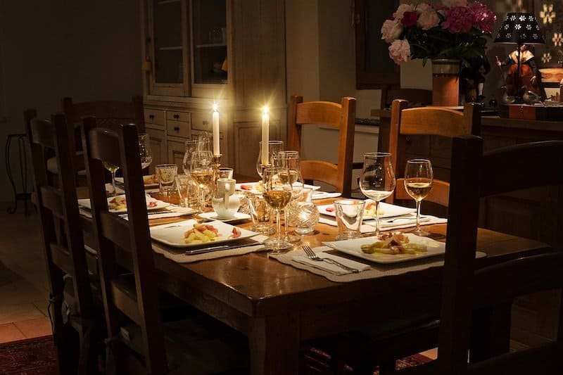 dining table set with plates and glasses with candles