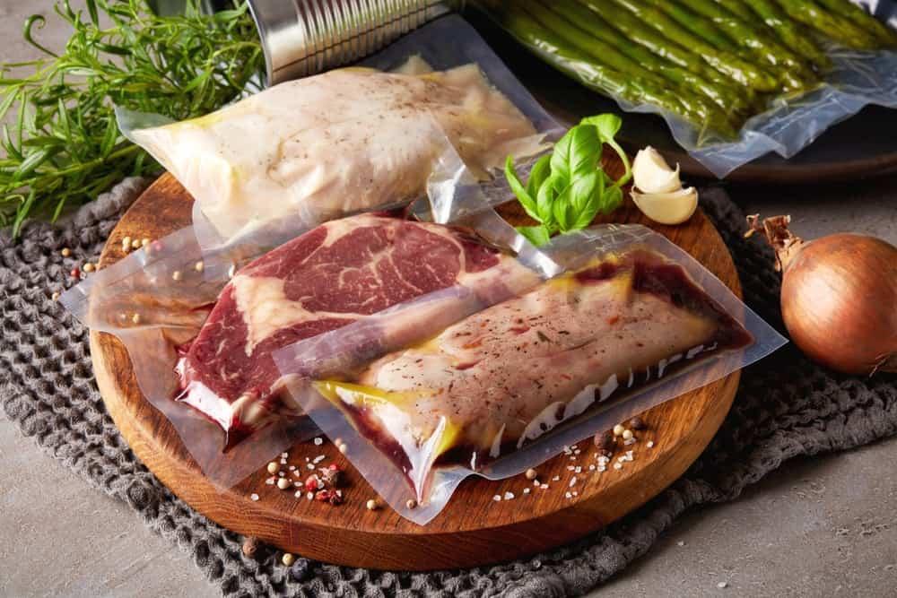 vacuum sealed chicken steak and pork on chopping board with seasonings
