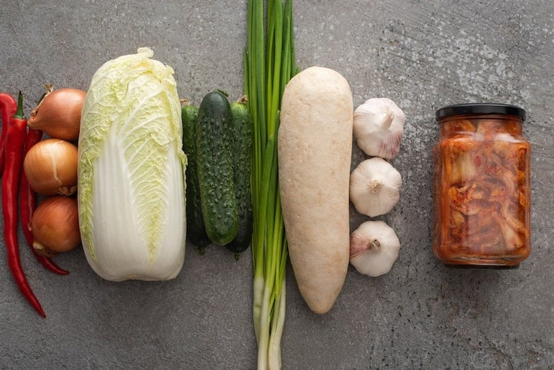 red chili peppers, onions, cabbage, cucumber, green onion, garlic, and jar of kimchi all in a row
