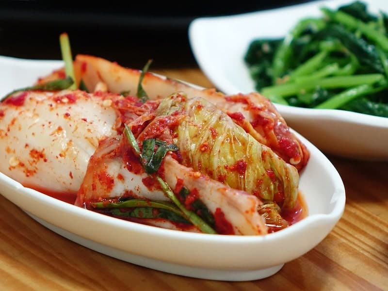 white oval plate with kimchi and plate with vegetables in background