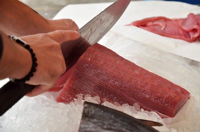 fish monger cutting tuna