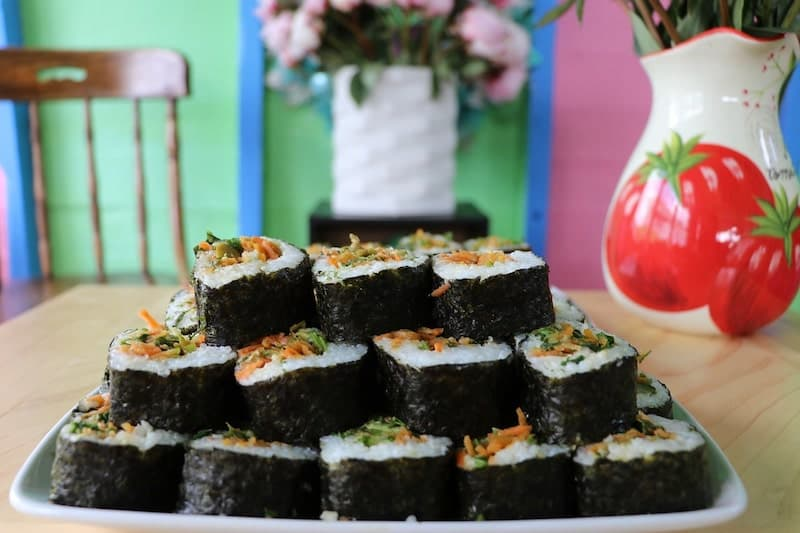 sushi stacked on plate on dining table