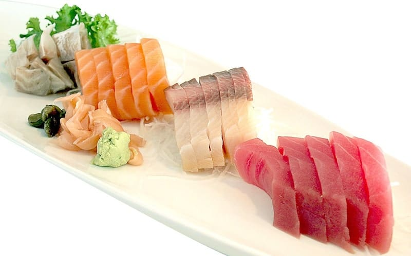 plate of 4 types of sashimi with ginger and wasabi